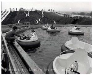 Barn i runda gummibåtar i en bassäng.