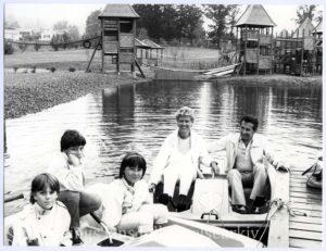 Tre barn och två vuxna i trampbåtar. I bakgrunden klätterställningar.