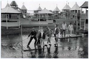 Två flottar med barn drar sig över ett vattenhinder.