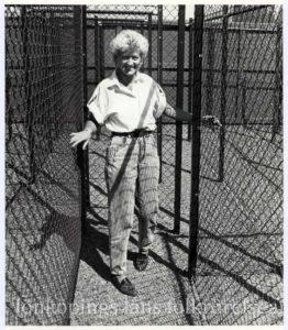 En kvinna går står i en gång med stängsel på båda sidor.