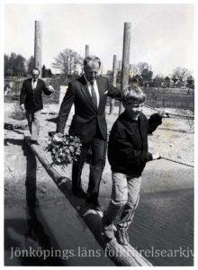 Två män och en pojke går balansgång på en stock.