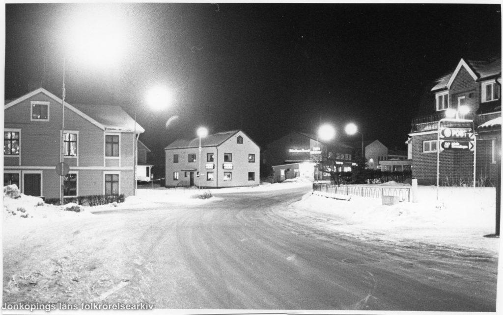 Vinterkvällsbild över tät bebyggelse vid en väg.