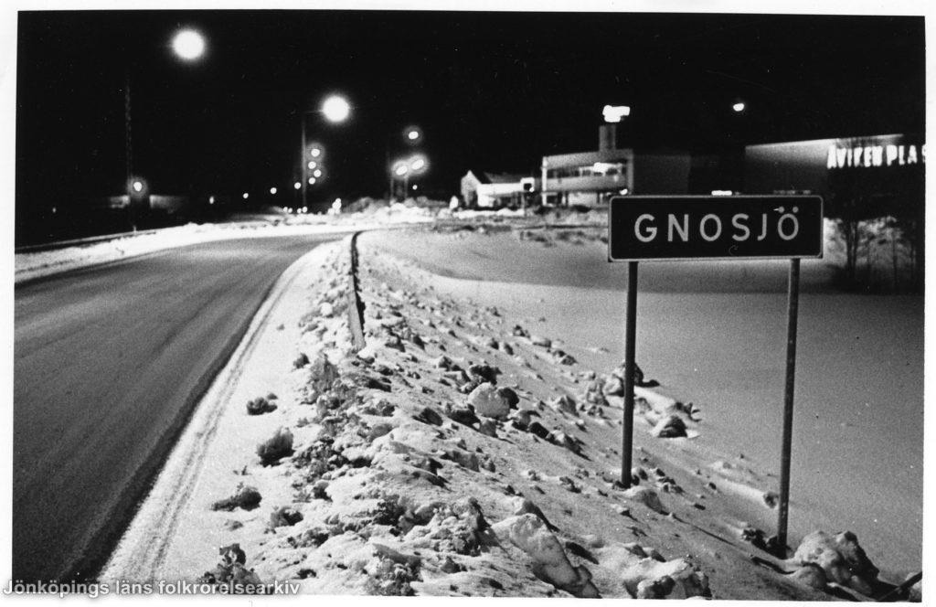 """Vinterkvällsbild över väg. Vid sidan av vägen en skylt med texten """"GNOSJÖ"""". I bakgrunden bebyggelse."""