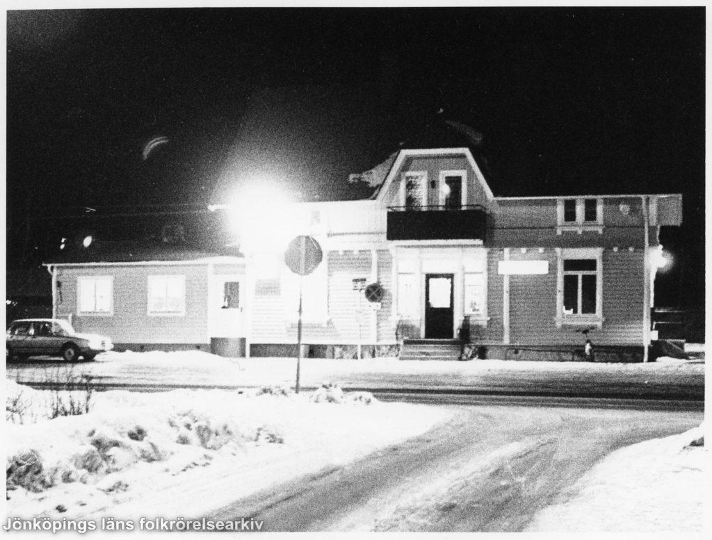 Vinterkvällsvy över upplyst byggnad.