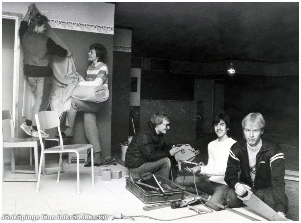 Fem personer arbetar på en scen. Två av dem hänger upp ett draperi.