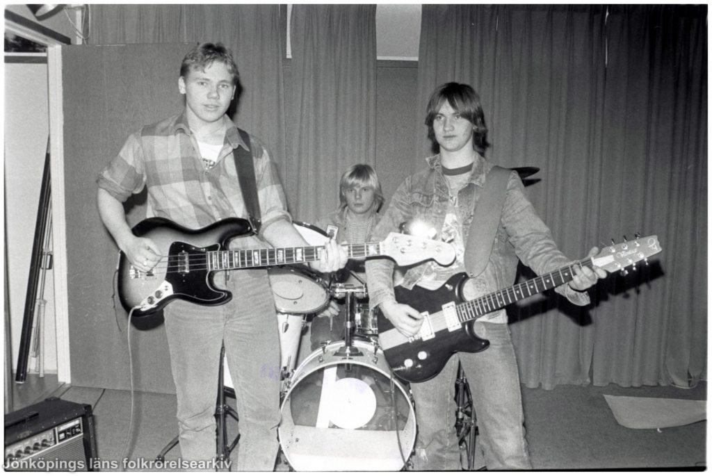 Tre unga män med musikinstrument på en scen. Två gitarrer och ett trumset.