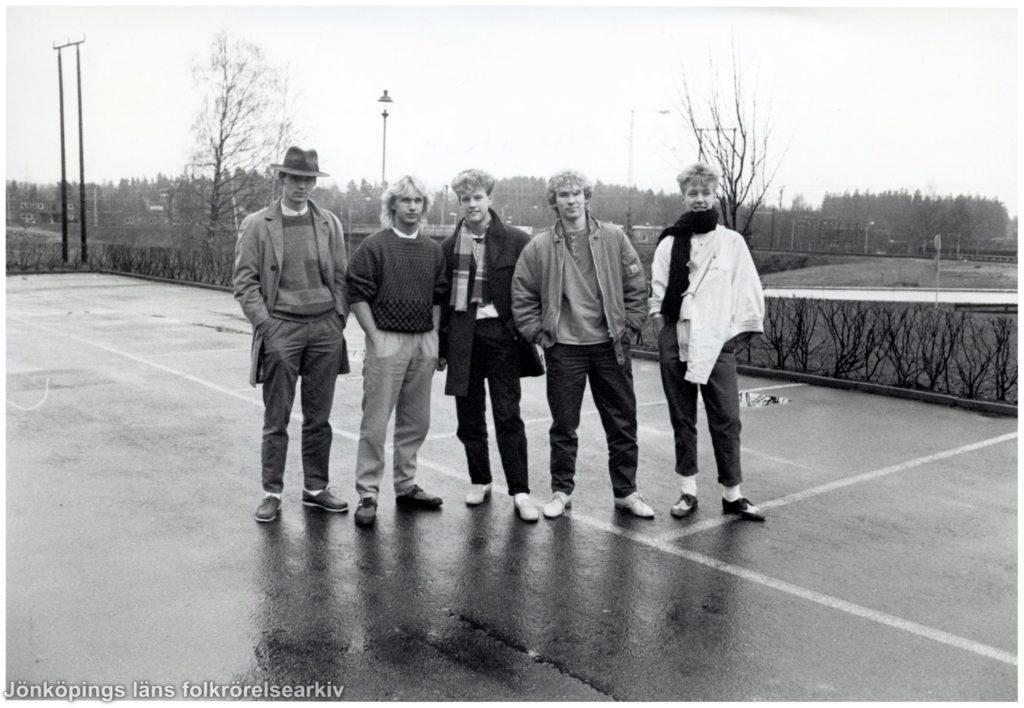 Fem unga män står på en regnvåt parkering.