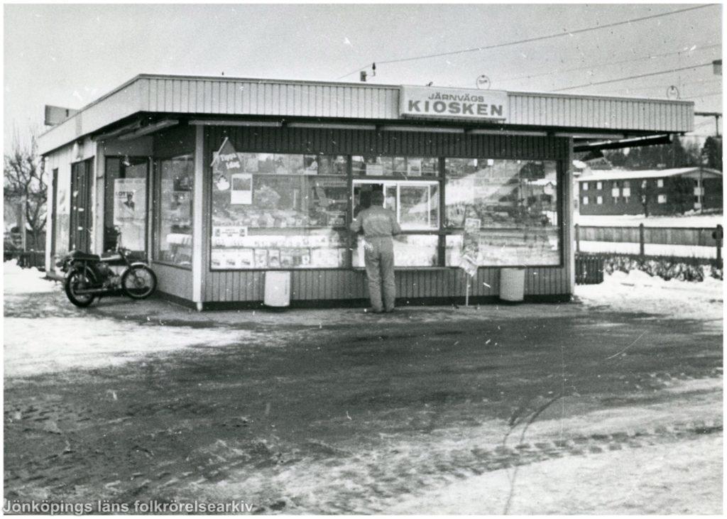 En person står vid en kiosklucka med ryggen mot kameran.