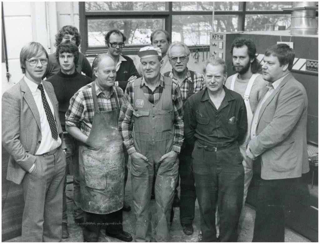 En grupp arbetare uppställda för foto i en industrilokal.