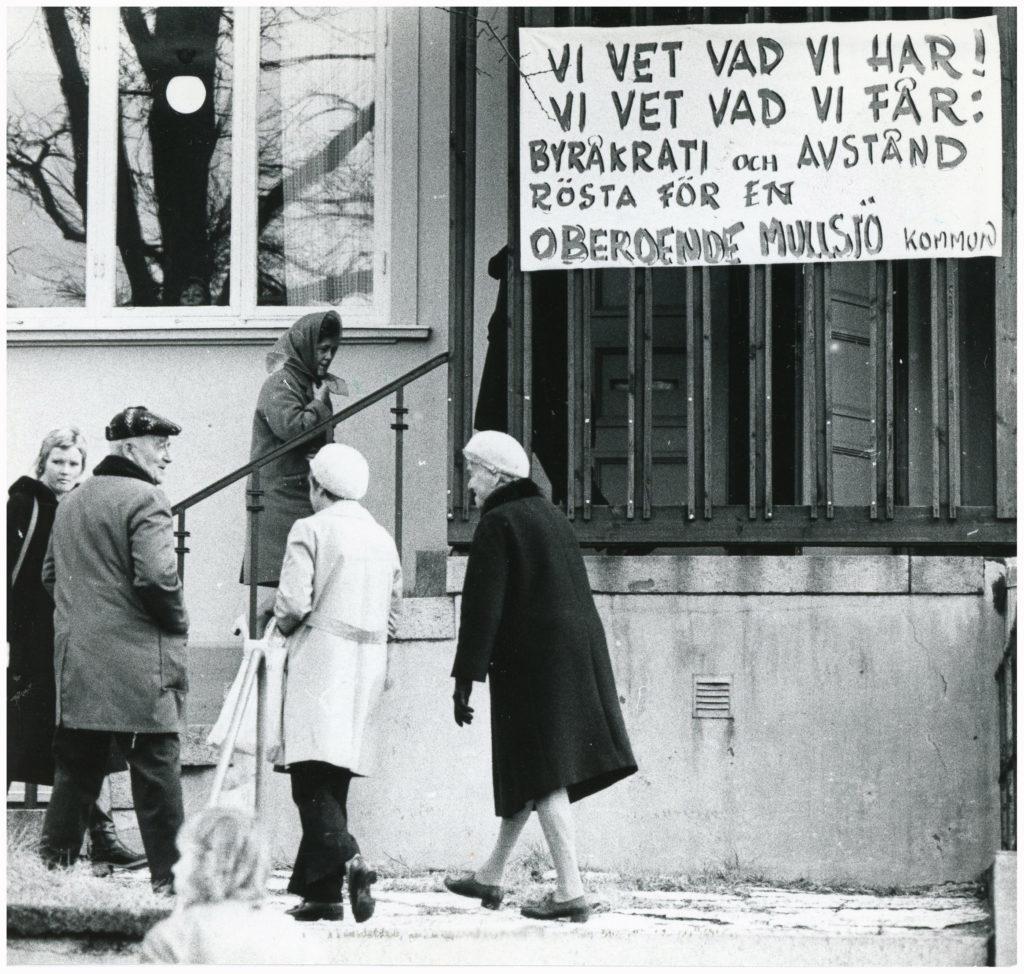 En grupp äldre människor på väg uppför en trappa. Vid trappan en skylt som uppmanar till att rösta för ett oberoende Mullsjö.