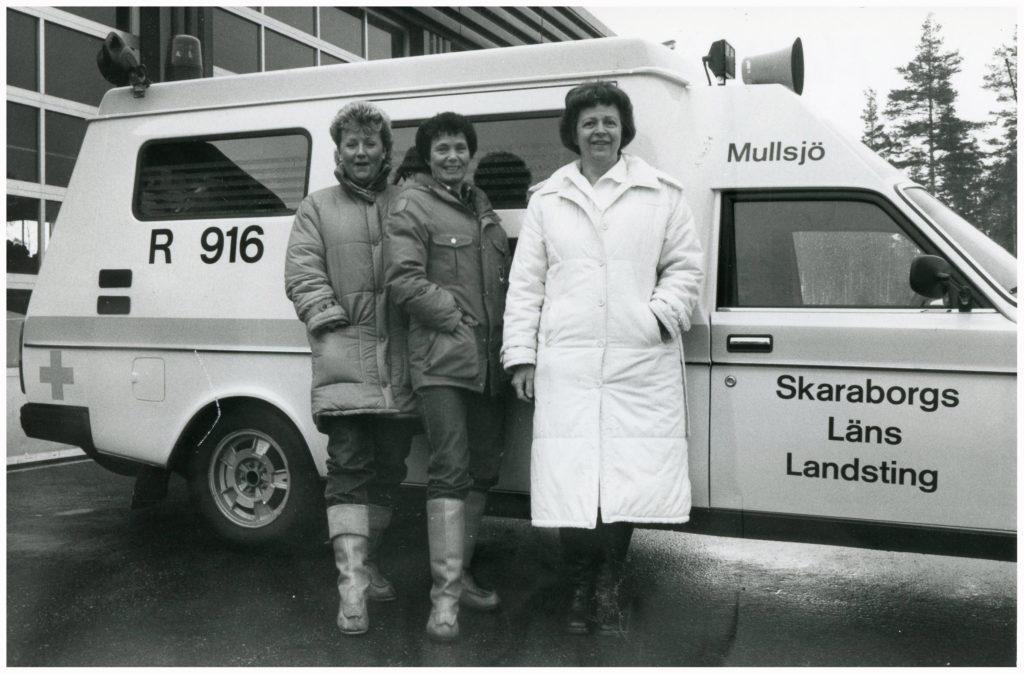 Tre kvinnor framför en ambulans.