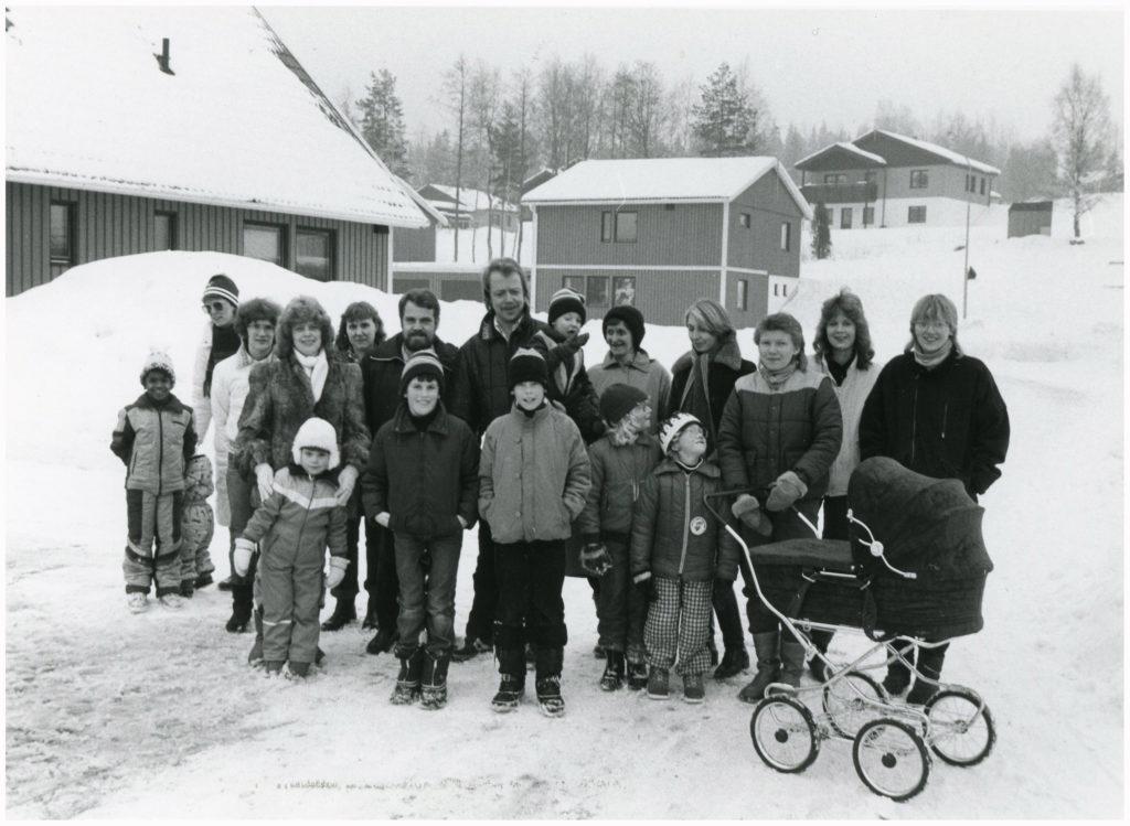 Ett tjugotal människor, barn, unga och vuxna, uppställda framför ett bostadsområde i vinterskrud.