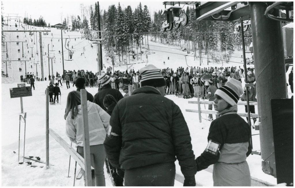 En folkmassa vid foten av en skidbacke.