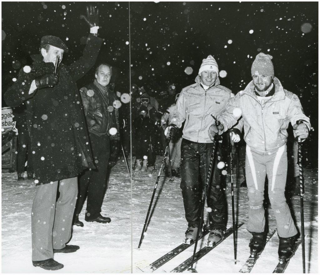 En man håller upp handen framför två stycken män i skidutrustning. Det är kväll och snön faller.