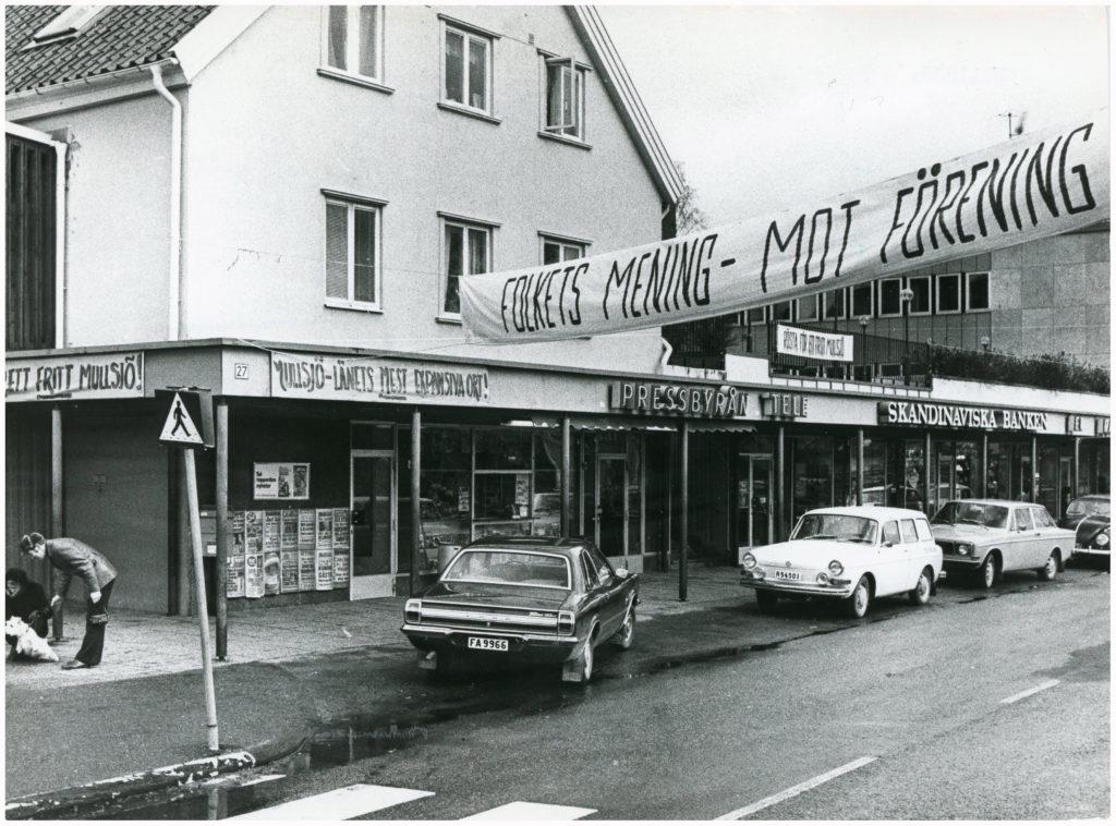 """Bilar parkerade framför Pressbyrå och Skandinaviska Banken. Över gatan en banderoll med texten """"Folkets mening - mot förening""""."""