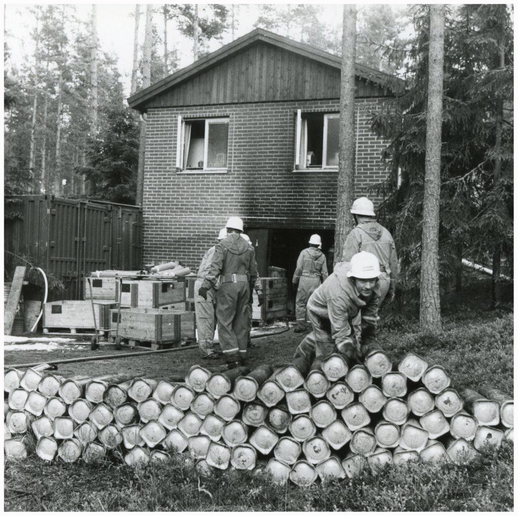 Brandmän i arbete vid en brandskadad byggnad. I förgrunden ligger ett 70-tal tuber med gas.