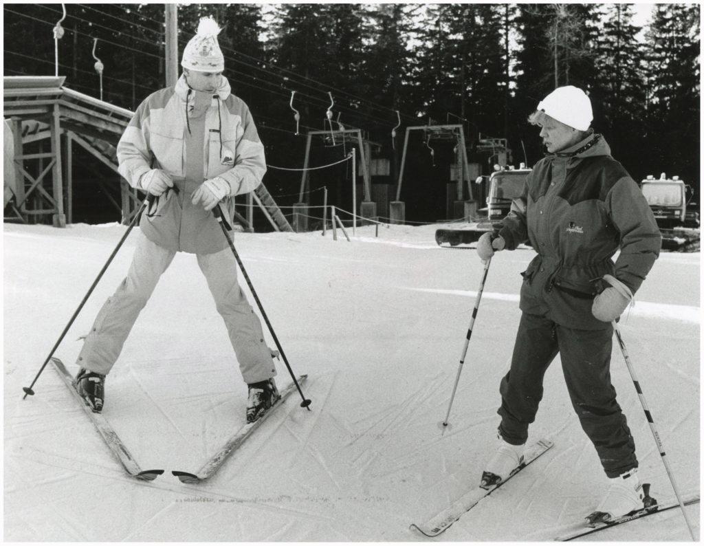 En man och en kvinna i en skidbacke. I bakgrunden liftanordning.