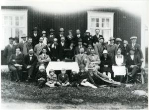 Ett trettiotal uppklädda människor unga som gamla stående och sittande framför ett hus med träfasad.