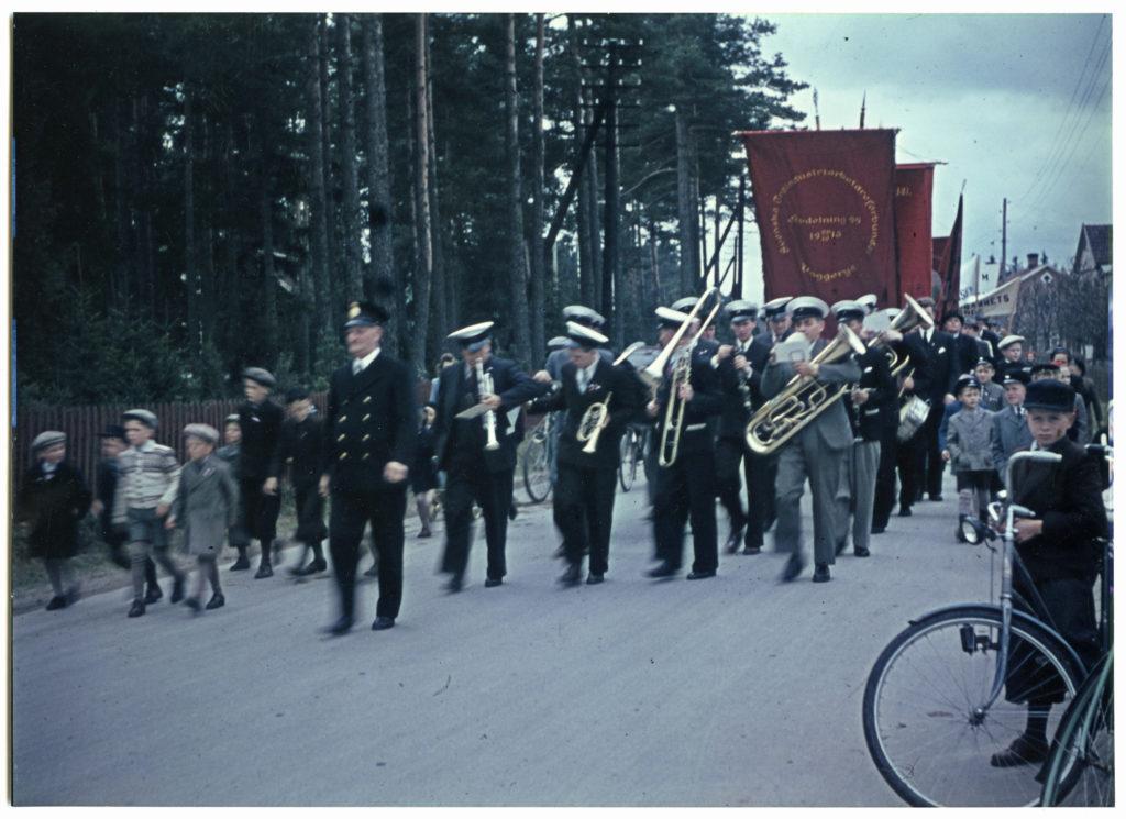 Demonstrationståg med musikanter och fanor går på en väg kantad av åskådare på ena sidan och skog och staket på andra sidan vägen.