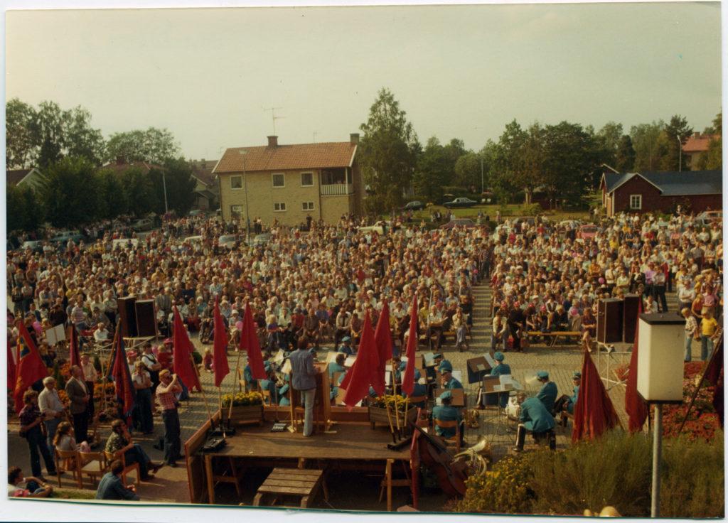 På bilden syns ryggtavlan på en man som står på ett podium och talar inför ett folkhav. Podiet är kantat av röda fanor. I bakgrunden hus, bilar och träd.