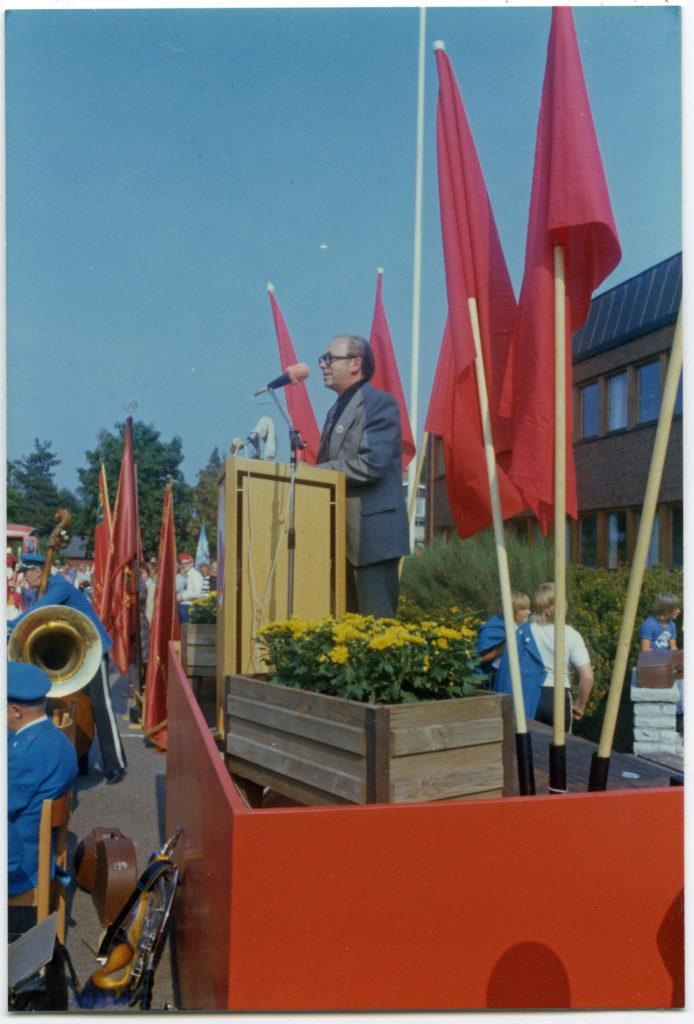 En man står på ett podium kantat av röda fanor och talar inför åhörare.