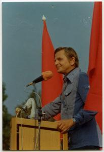 En man i halvfigur står vid en mikrofon. Två röda fanor skymtar vid hans sida.