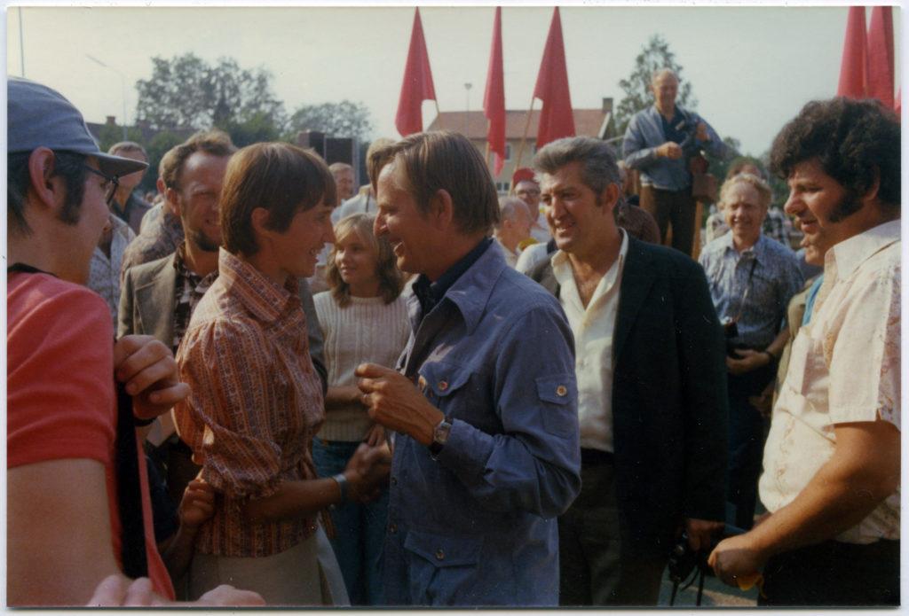 Ett möte mellan en man och en kvinna omgivna av en grupp med människor. Röda fanor skymtar i bakgrunden.