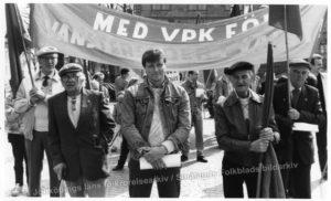 En yngre man i jeansjacka kantad av fyra äldre herrar som håller i banderoller.
