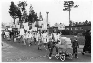 Demonstrationståg. Blandade åldrar. Några kör barnvagn. Några bär plakat.