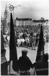 Foto taget ut över publikhav som samlats på ett torg. I bakrunden ett kyrktorn. I förgrunden ryggen på några män och kvinnor som håller i fanor.