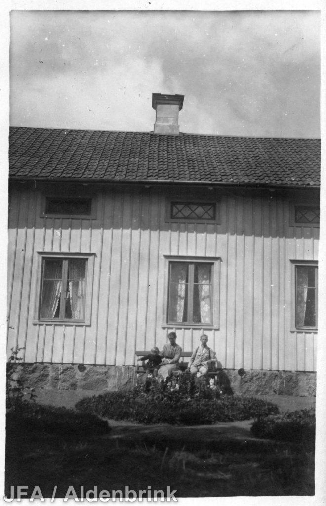 En man och en kvinna och ett litet barn sittande på en bänk vid väggen till ett trähus.