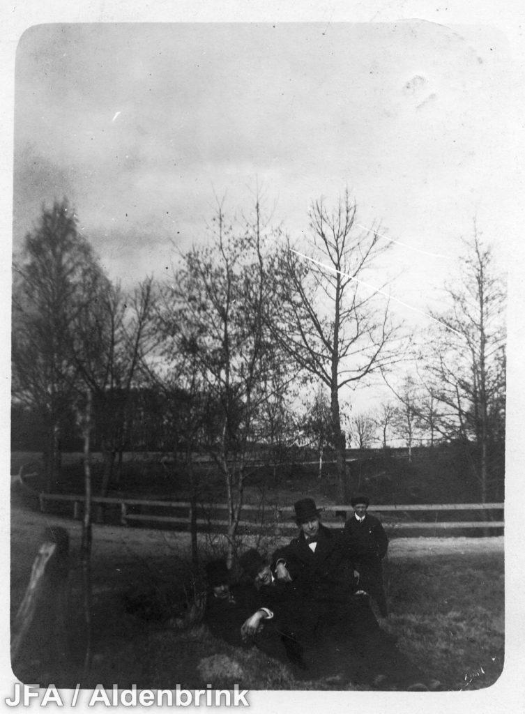 Fyra yngre män framför en väg som på ena sidan kantas av ett trästaket.
