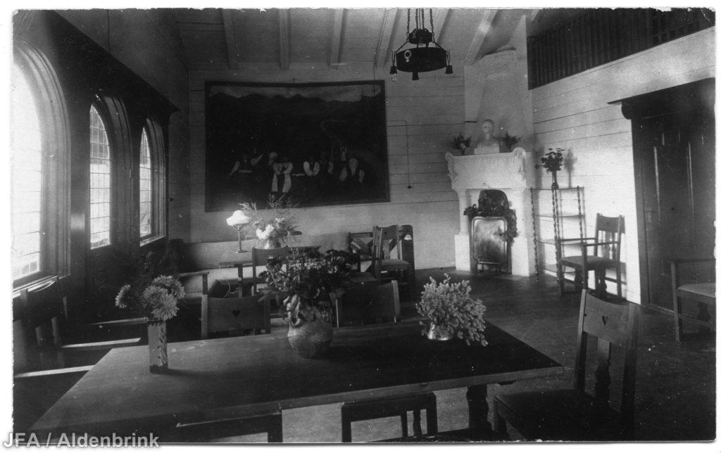 Interiörbild av gammalt hus. I förgrunden ett bord med stolar. I bakgrunden en stor tavla på en vägg vid en eldstad.