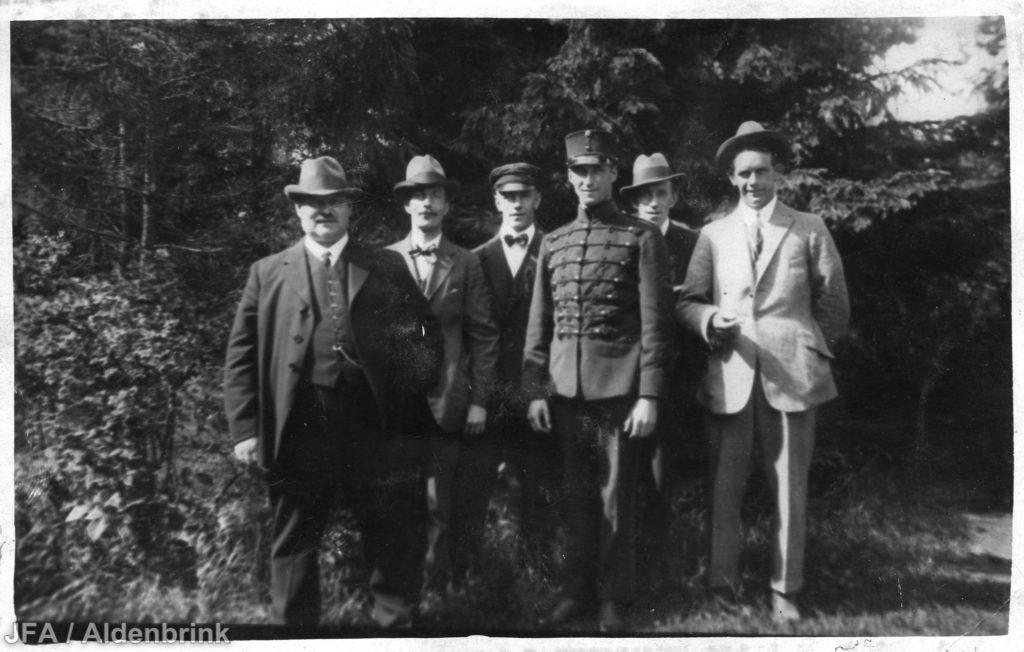 Sex män uppställda för foto framför skogsparti.