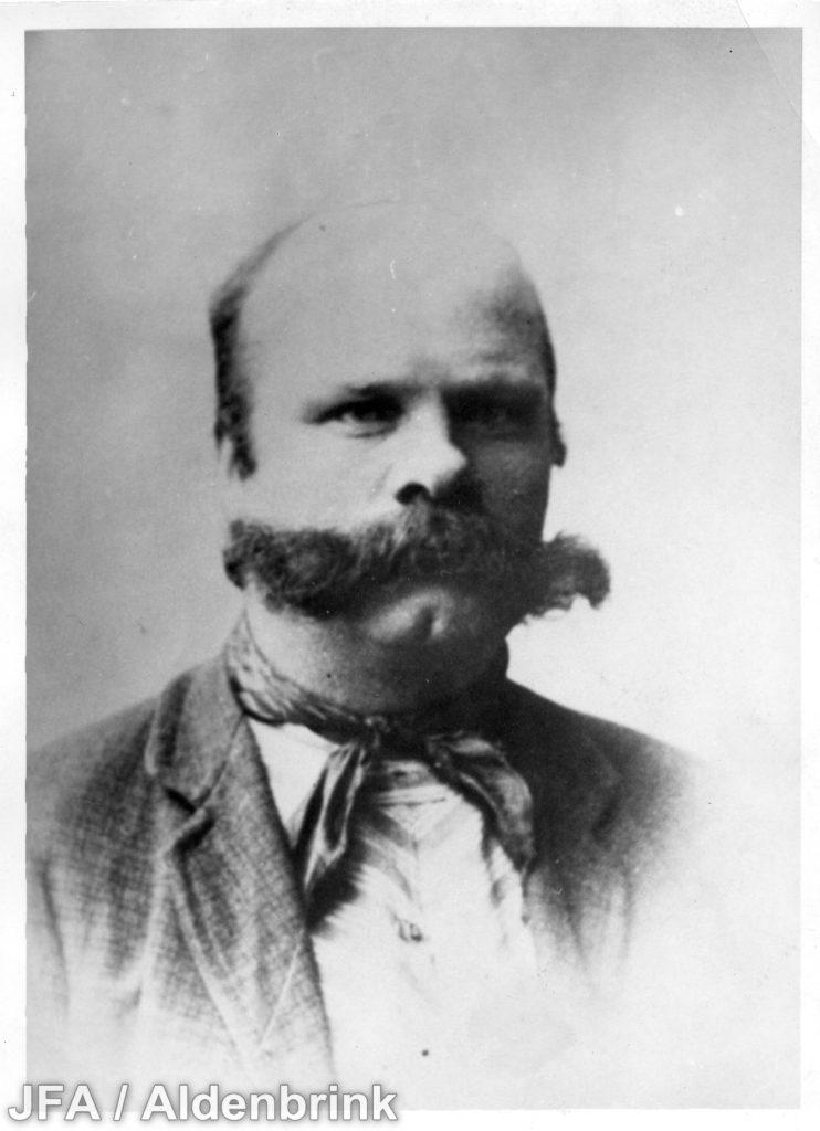 Porträtt av skallig man med stora mustascher.