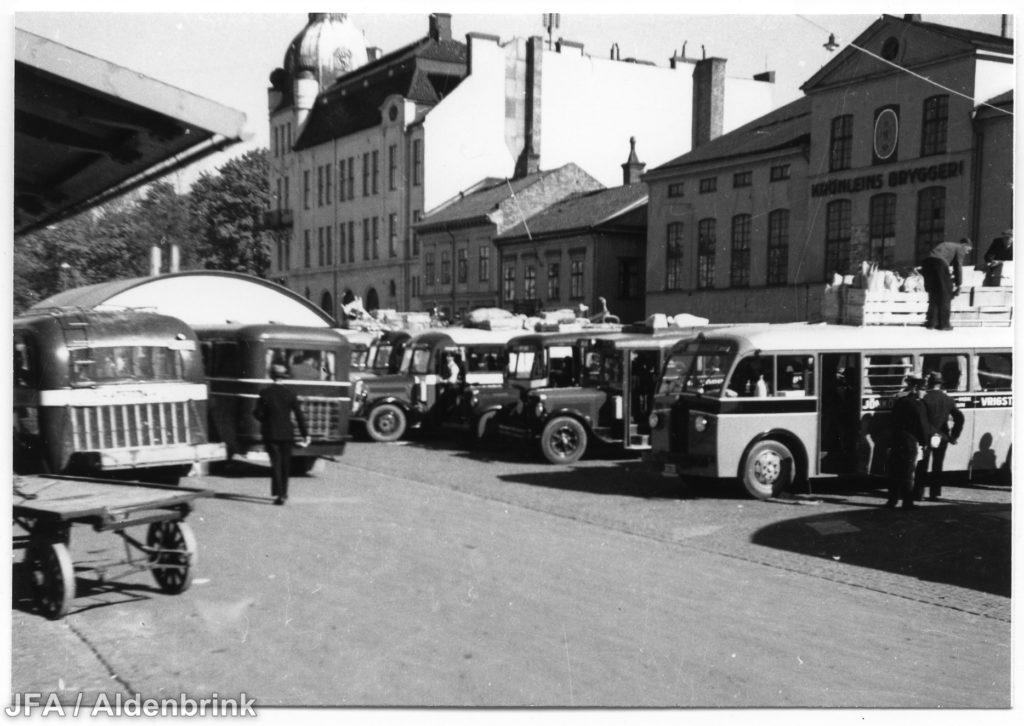 Ett tiotal bussar uppställda på torg framför hus.