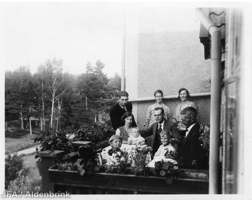 Runt tio personer samlade på en altan, både män, kvinnor och barn.