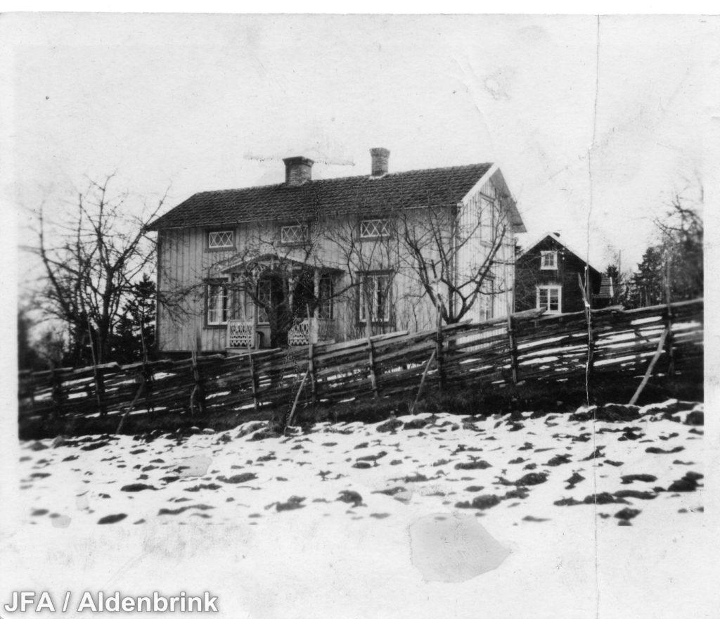 Mindre vitmålad stuga i backe. Framför stugan en gärdesgård. På marken ligger snö.
