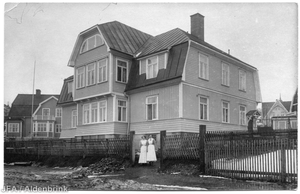 Stort trähus. Två personer står framför huset.