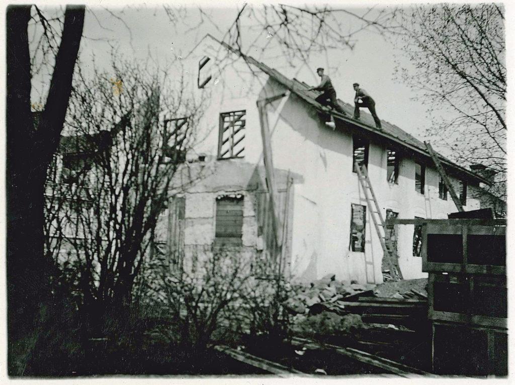 Två män lägger pannor på ett tak på ett vitt tvåvåningshus. Mot ena väggen står en stege.