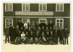 """Ett tjugotal människor står framför en träbyggnad med en skylt """"Möbelfabriken Göta"""". På marken ligger snö."""