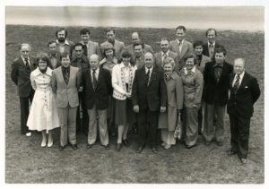 Foto taget snett ovanfrån på en grupp människor som står på en gräsmatta.