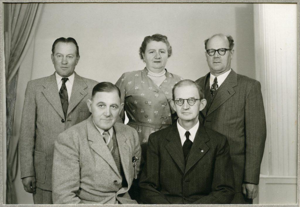 Svartvitt studio foto på fyra män och en kvinna.
