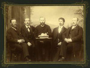 Fem män sitter i en fotostudio. I bakgrunden skymtar en fond med skog och berg.
