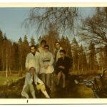 6 kvinnor sitter och står på en liten kulle. I bakgrunden skymtar ett fält och skog. I förgrunden skymtar styret på en cykel.