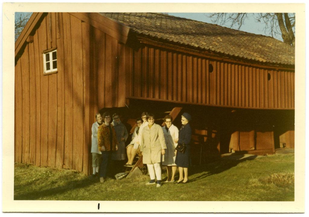 8 kvinnor uppställda framför en röd träbyggnad som ser ut att var en lada.