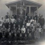 """Svartvit foto på grupp människor, både män, kvinnor unga och gamla uppställda framför entrén till en träbyggnad. I mitten ett standar med texten """"Nya krafter""""."""