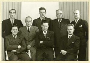 Åtta män uppställda för foto. I bakgrunden ett draperi.