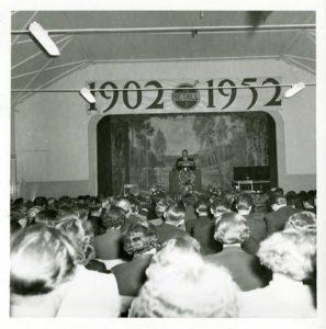 Vy över sittande publik taget bakifrån. Längst fram en man vid en pulpet på en scen. Ovanför scenen texten 1902 -1952.