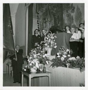 En grupp kvinnor på en scen. Nedanför scenen en man som håller i en fana.